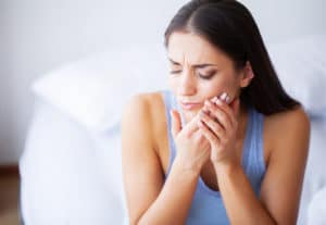 Tooth Pain. Woman Feeling Tooth Pain. Closeup Of Beautiful Sad Girl Suffering From Strong Tooth Pain. Attractive Female Feeling Painful Toothache. Dental Health And Care Concept.